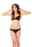 Boos slank meisje die een metende band bijten Stock Fotografie