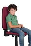 Boos weinig jongenszitting op grote stoel royalty-vrije stock afbeelding