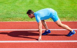 Boost speed concept. Man athlete runner push off starting position stadium path sunny day. Runner captured in motion royalty free stock photography