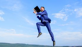 Boost speed online. Businessman laptop satisfied quality. Man with laptop jump or fly in air blue sky background. Excellent internet provider raise up quality stock photography
