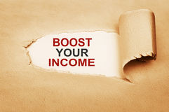 Boost Your Income Behind Torn Paper stock photo