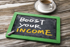 Boost your income. Handwritten on blackboard stock photo