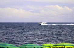 Boot aan de overzeese en strandparaplu's op het strand Stock Afbeeldingen