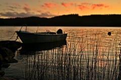 Boot auf dem See bei schwedischem Sonnenuntergang Lizenzfreie Stockfotos
