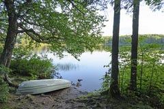 Boot auf dem Ufer von einem ruhigen See Lizenzfreie Stockfotografie