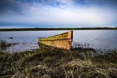 Boot auf der Flussbank bei Sonnenuntergang Stockbild
