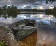 Boot auf Küste von hölzernem See Lizenzfreie Stockfotografie