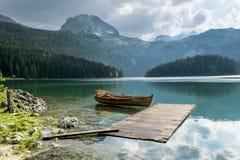 Boot auf schwarzem See im Nationalpark Durmitor und in den Bergen I Lizenzfreies Stockfoto