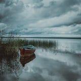 Boot auf See mit Bäumen und Scheune einer Reflexion lizenzfreies stockfoto