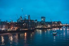 Boot auf Themse- und London-Skylinen nachts Stockbilder
