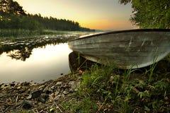 Boot auf Ufer im Sonnenaufgang Stockfoto