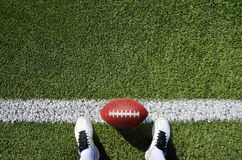 Boot and ball american football. High angle view shot of a american football player standing on the field with copy space Royalty Free Stock Image