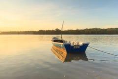Boot bei Sonnenaufgang mit Reflexion in Buntal-Dorf stockbilder