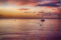 Boot bei Sonnenuntergang auf adriatischer Küste Stockfotografie