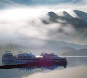 Boot, Berg und Wolke für Reisenhintergrund Stockfotografie