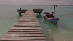 Boot bij pijler op kalm overzees tropisch eiland stock footage