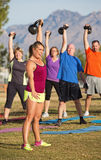 Boot Camp Exercise Class Lifting Weights. Boot camp exercise class lifting kettle bell weights Stock Photography