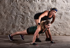 Boot Camp Trainer with Woman. Bootcamp workout coach helps women with push ups Royalty Free Stock Photos