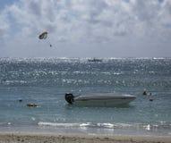 Boot, das auf Strandfront Drachensurfer, mit wispy blauem Himmel und Surfer im Hintergrund wartet stockfoto