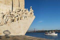 Boot, das durch das Monument des Entdeckungen Padrao DOS Descobrimentos im Tajo in Lissabon, Portugal, die 25 von überschreitet Lizenzfreie Stockbilder