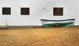 Boot, das an einer weißen Wand sich lehnt Stockfotografie