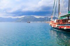 Boot in de zeehaven van Marmaris met bergen over wolken Stock Foto