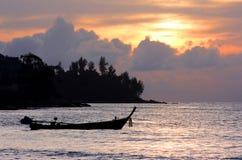 Boot des langen Hecks mit orange Himmel Stockbilder
