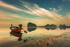 Boot des langen Schwanzes über buntem Himmel auf dem Strand Stockfotos