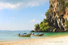Boot des langen Schwanzes auf tropischem Strand mit Kalksteinfelsen, Krabi, Thailand Stockfotos