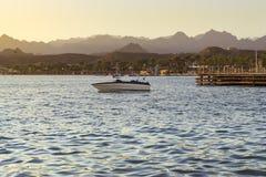 Boot dichtbij een houten pijler op het strand in de avond in Sharm Gr Stock Fotografie