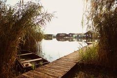 Boot dichtbij houten weg op meer Stock Afbeeldingen
