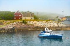 Boot dichtbij kust met huizen in Noorwegen Stock Afbeeldingen