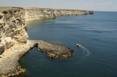 Boot dichtbij mooie rotsachtige zonnige kust Stock Fotografie
