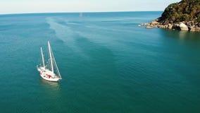 Boot dichtbij tropische kust Verbazende hommelmening van modern jacht dat bij het kalme zeewater dichtbij kust van tropische vulk stock video