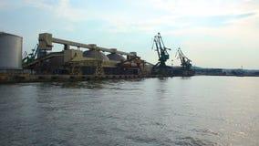 Boot die door overzees, naderbij komende werf met immense pakhuizen en kranen gaan bij haven stock videobeelden