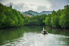 Boot die met mangrovebos vissen Stock Foto's