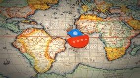 Boot die op de wereldkaart drijven Stock Foto's