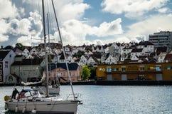 Boot die op het overzees in de voorgrond met schilderachtige huizen op de achtergrond in de jachthavenhaven van Stavanger varen stock afbeelding