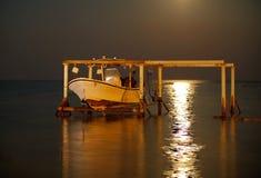 Boot die Post herstellen die door super maanlicht bij Asker-strand Bahrein 15 November, 2016 wordt aangestoken Stock Afbeeldingen