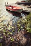 Boot am Dock auf kleinem See lizenzfreie stockbilder