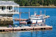 Boot am Dock mit bunten Picknicktischen Stockbilder