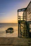 Boot en Houten Treden door het Overzees tijdens Zonsondergang Stock Foto's