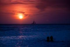 Boot en silhouetten bij zonsondergang Stock Foto's