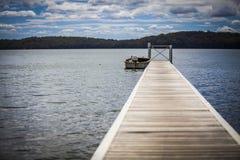 Boot am Ende des Piers auf See Lizenzfreies Stockfoto