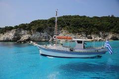 Boot in erstaunlichem sauberem blauem Wasser nahe Paxos-Inselfliegen um es stockbild
