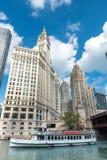 Boot fährt auf Chicago River zwischen Wolkenkratzer herein in die Stadt lizenzfreies stockbild