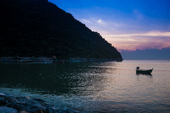 Boot festgemacht nahe der Küste bei Sonnenaufgang Lizenzfreie Stockfotos