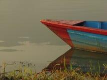 Boot gebunden am Ufer von Fewa See lizenzfreie stockfotografie