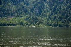 Boot geht entlang das Ufer von einem Gebirgssee Stockfotografie