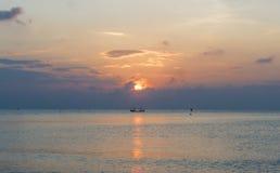 Boot in het Overzeese Zonsondergangstrand stock afbeelding